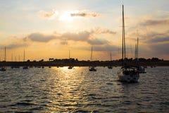 在一条小河的停住的小船在日落 库存图片