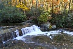 在一条小河的小瀑布在秋天 免版税图库摄影