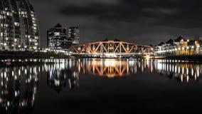 在一条小河的桥梁有长的反射的 免版税库存照片
