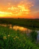 在一条小河的河岸的日落 库存照片