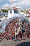 在一条小船前面的捕鱼网在港口在阳光下 库存照片