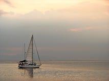 在一条小船或游艇的日落在风平浪静 库存图片