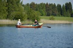 在一条小船有钓鱼竿的-赫尔辛基,芬兰的年长夫妇划船- 2015年6月 免版税库存照片