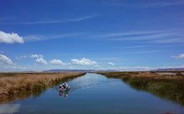 在一条小船的一个家庭航行从浮动海岛 免版税库存图片