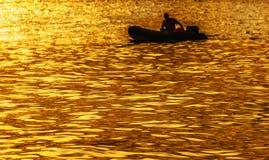 在一条小船的剪影在金黄日落 图库摄影
