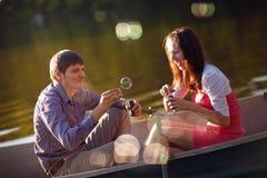 在一条小船的夫妇与泡影吹风机 免版税图库摄影