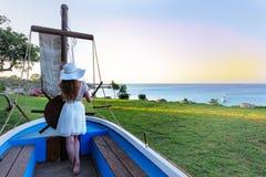 在一条小船的女孩航行在海岛岸 免版税库存图片