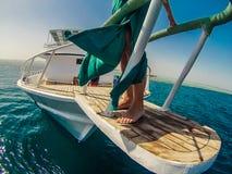在一条小船的女性脚在海洋 免版税库存图片