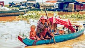 在一条小船的家庭在Tonle Sap湖的一个浮动村庄 免版税库存照片