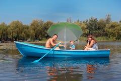 在一条小船的家庭骑马在夏天 图库摄影