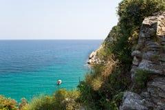 在一条小船的海视图在蓝绿色峭壁,Doumuchari拉古纳,希腊水和片断  免版税库存照片