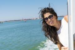 在一条小船的美好的微笑的妇女航行有在头发的风的 免版税库存照片