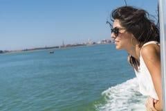 在一条小船的美好的微笑的妇女航行有在头发的风的 图库摄影