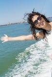 在一条小船的美好的微笑的妇女航行有在头发的风的 库存照片