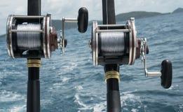 在一条小船的钓鱼竿在蓝色海和天空 图库摄影