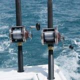 在一条小船的钓鱼竿在蓝色海 免版税图库摄影