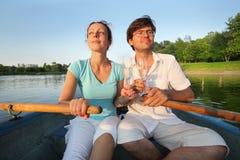 在一条小船的年轻夫妇有玻璃的 免版税库存图片