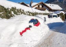 在一条小街道的汽车在准备好的雪下被清洗,加米施・帕藤吉兴,巴伐利亚,德国 免版税库存图片
