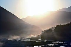 在一条山河的背景的晴朗的黎明山的 库存照片