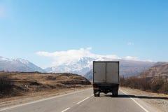 在一条山高速公路的货物汽车在与蓝天和山的岩石旁边在背景中 概念  库存照片