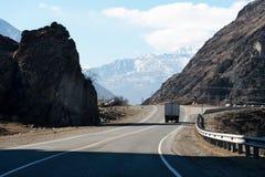 在一条山高速公路的货物汽车在与蓝天和山的岩石旁边在背景中 概念  免版税库存图片