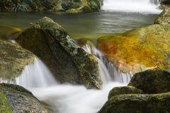 在一条岩石小河的美丽的五颜六色的小瀑布 库存图片