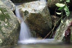 在一条岩石小河的美丽的小瀑布 库存图片
