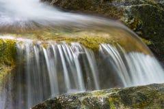在一条岩石小河的美丽的小瀑布 免版税库存图片