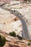 在一条岩石沙漠高速公路的汽车在南犹他 免版税库存照片