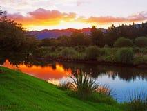 在一条平静的小河的日落 免版税库存图片