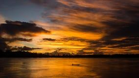 在一条微小的小船后的日落在亚马孙河 库存图片