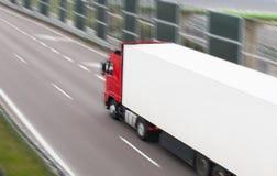 在一条快速途径的红色白色卡车,行动迷离 免版税库存图片