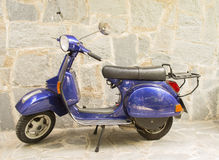 在一条扔石头的街道上的蓝色摩托车 库存照片