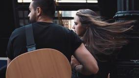 在一条拥挤的街的千福年的浪漫夫妇拥抱 欧洲人用吉他和女孩举行手 吹在头发4K的风 股票录像