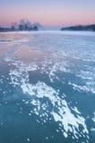 在一条有薄雾和结冰的河的抽烟的烟囱在黄昏期间 免版税库存图片