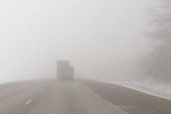 在一条有雾的路的卡车 免版税库存图片