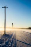 在一条有雾的雪路的电线杆 库存图片