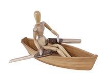 在一条木小船的人划船 免版税图库摄影