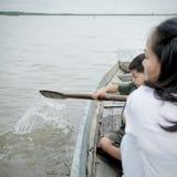 在一条木小船的小男孩划船在湖:关闭 免版税库存照片