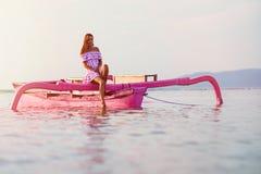 在一条桃红色小船的被晒黑的女孩游泳 免版税库存照片