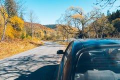 在一条森林道路的汽车在山 免版税库存图片