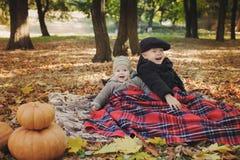 在一条毯子下的兄弟在室外的秋天 免版税库存图片