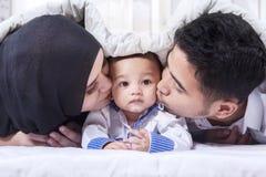 在一条毯子下的美丽的家庭在床上 免版税图库摄影