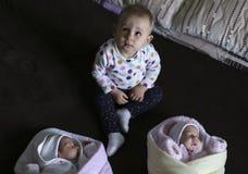 在一条毯子的新出生的孪生有他的岁姐妹的 库存图片