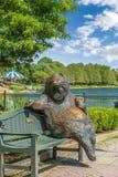 在一条河旁边的熊雕象长凳的 图库摄影