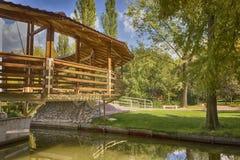 在一条河的圆的木桥散步在秋天 免版税库存照片