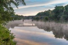 在一条河的壮观的日出有桥梁的 库存图片