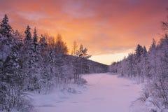 在一条河的日出在莱维,芬兰拉普兰附近的冬天 库存照片