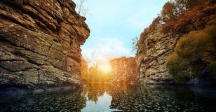 在一条河的日落有岩石岸的 免版税图库摄影