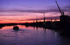 在一条河的美好的五颜六色的黄昏有驳船和起重机剪影的  库存图片